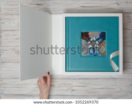 Photo album in a cardboard box. photo book with leather cover. womans hand open box with photo album. the person is looking at the photo book