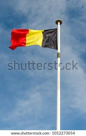 A belgium flag is floating in a blue sky #1052273054