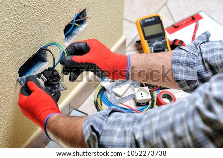 Electrician technician at work sticks the cable between the clamps of a socket in a residential electrical installation #1052273738