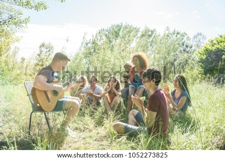 group of friends play guitar, sing, making music outdoors in the park on a weekend trip