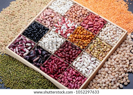 Different types of legumes. In wooden box.Varieties of beans.Small red bean,Scarlett runner bean Phaseolus coccineus ,butter bean,kidney bean,pinto and other sorts of beans.Top view.On dark stone #1052297633