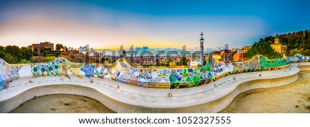 Mosaic tile panorama and Barcelona cityscape in famous park Guell at summer sunset,Spain #1052327555