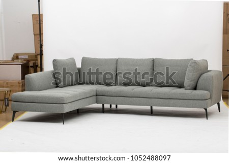 Frontal view of a a living room in an apartment with a large gray sofa bed, #1052488097