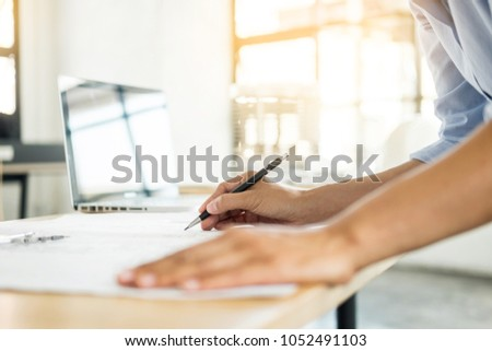 Person's engineer Hand Drawing Plan On Blue Print with architect equipment, Architects working at the table #1052491103
