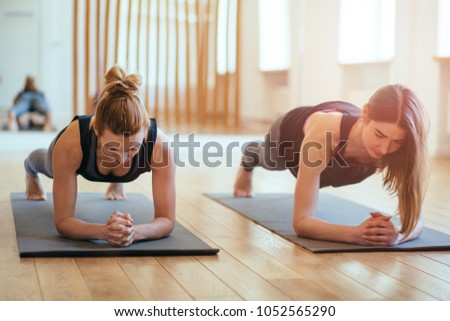Front view of two sporty fit and slim middle aged women doing planking exercise indoors together with a natural light in modern interior sport studio hall or yoga class. #1052565290