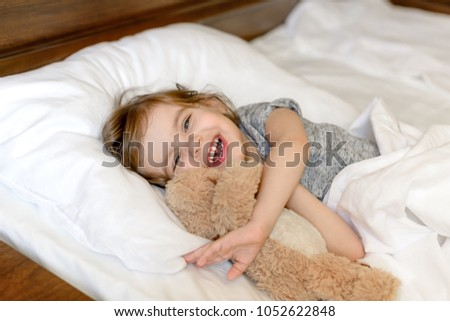 Active adorable baby wakes up lying in bed with her Teddy bear toy, soft white linens. Children's day. World Smile Day. Start the morning right! Start the morning with a smile! #1052622848
