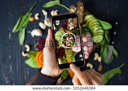 Woman hands takes food photo of mixed healthy buddha bowl on wooden board with vegetables and dip cashew sauce. Makes food photography for social networks with phone. Raw, vegan, vegetarian food #1052648384