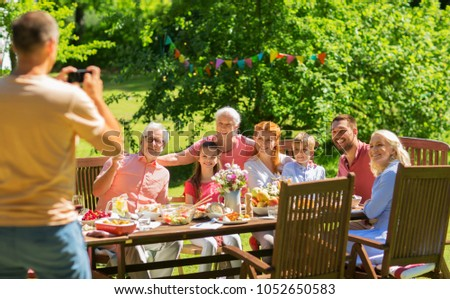leisure, holidays and people concept - happy family having festive dinner or summer garden party and photographing by smartphone