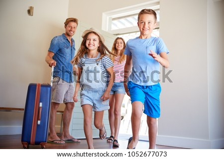 Family Arriving At Summer Vacation Rental Royalty-Free Stock Photo #1052677073