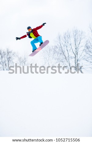Photo of sportive man in helmet with snowboard jumping in snowy resort #1052715506