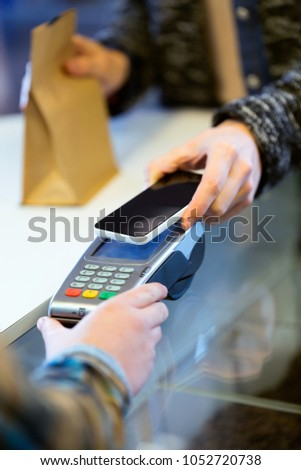 Portrait of customer using her smartphone to make mobile payment with electronic reader. #1052720738