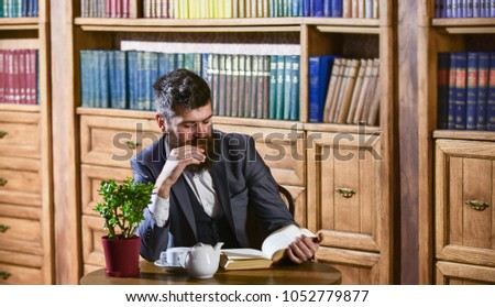 Aristocrat on thoughtful face reading book. Oldfashioned man near cup, teapot. Man in classic suit sits in vintage interior, library, book shelves on background. Aristocratic lifestyle concept. #1052779877