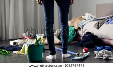 Woman horrified by mess left after party in her apartment, cleaning service Royalty-Free Stock Photo #1052789693