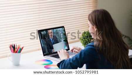 Digital composite of Businesswoman video conferencing with colleague on laptop #1052795981