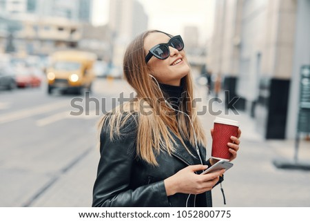 Pretty girl stand on the street listen music from her headphones and drink coffee, windy weather #1052800775