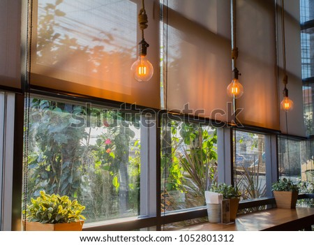 roll blinds to protect sunlight and lighting to decorate the coffee shop. Royalty-Free Stock Photo #1052801312