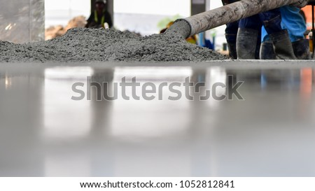 Construction worker Concrete pouring during commercial concreting floors of building in construction site and Civil Engineer #1052812841