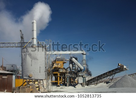 Equipment and details of a rock stone crushing complex against a blue sky, close-up. Mining industry. Quarry mining equipment. #1052813735