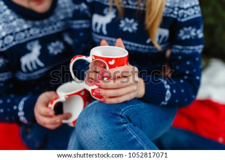 Mug of hot tea with a picture of a heart in the hands of a young couple in warm sweaters sitting on a red blanket. Wedding trip picnic outdoors in the winter in the woods or mountains. #1052817071