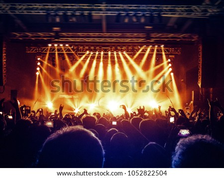 Big show stage in a concert venue with ecstatic fans raising hands. #1052822504