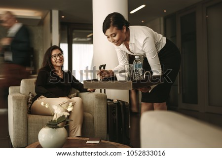 Business lounge waitress serving coffee to female passenger at waiting area. Business woman relaxing and waiting for flight at airport departure lounge. #1052833016
