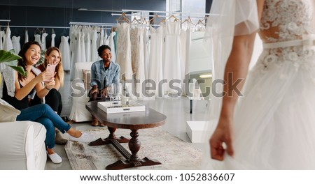 Women taking photographs of a female friend trying on wedding dress. Women in wedding dress fitting room. #1052836607