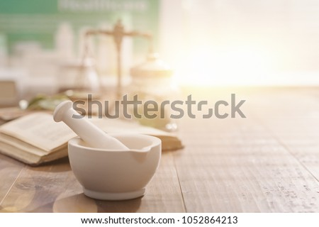 Mortar and pestle with pharmaceutical preparations's book and herbs on a wooden pharmacist table, traditional medicine and pharmacy concept #1052864213
