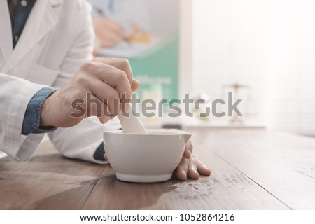 Professional pharmacist grinding a medical preparation using a mortar and pestle, pharmacy and medicine concept, hands close up #1052864216