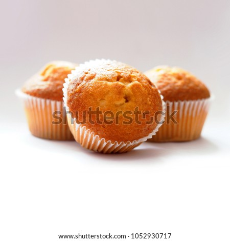 Freshly baked muffins. Three  muffins in wax liner on light background. Small biscuit tasty cupcakes, delicious #1052930717