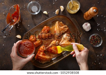 Hands brush baked wings with the bbq souce. Step by step recipe of homemade bbq wings top view. #1052938508