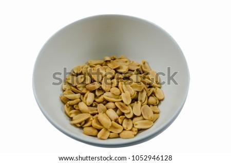 Peanuts sprinkle salt in a white cup. #1052946128