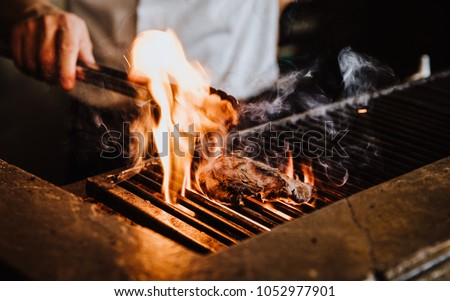 Steak on the grill with flames Royalty-Free Stock Photo #1052977901