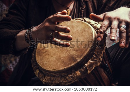 ethnic percussion musical instrument jembe and male hands Royalty-Free Stock Photo #1053008192