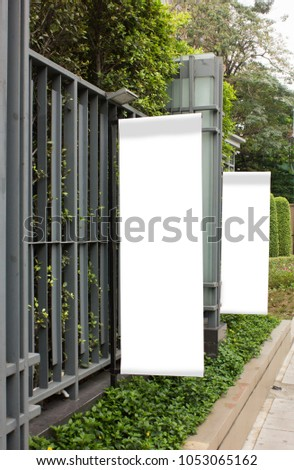 Vertical banners are hanging on metal line fence which covered with greenery plant.