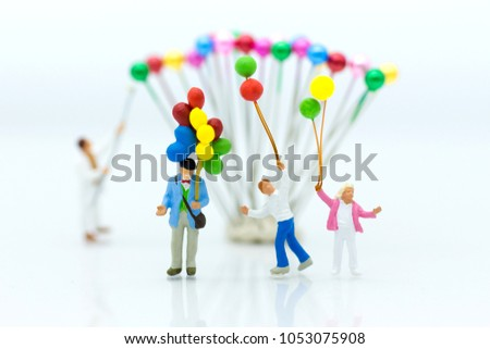 Miniature people: Childrens play balloon together wiht fun, using as background International day of families concept. #1053075908