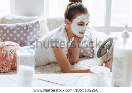 12 years old preteen relaxing on the sofa and making clay facial mask. Teenage girl doing anti blemish skin treatment. Morning skin care routine.