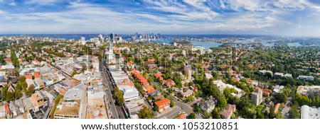 Distant Sydney city CBD and North Sydney on shores of Harbour in wide aerial panorama from residential local lower north shore suburb Crows Nest on a sunny day. Royalty-Free Stock Photo #1053210851