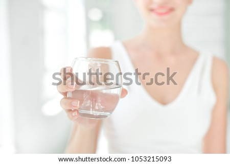 Female hands holding a clear glass of water. Slime body on background. Royalty-Free Stock Photo #1053215093