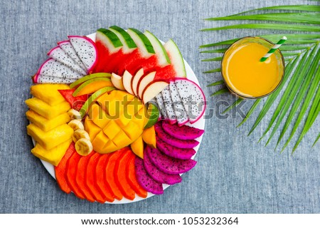Tropical fruits assortment on a white plate with fresh juice, textile grey background. Top view. Copy space. #1053232364