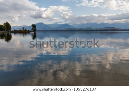 View over waters of Liptovska Mara lake with shore of Liptovsky Trnovec village and boats in Slovakia. Chocsky hills can be seen in the distance. #1053276137