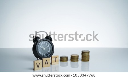 Value Added Tax (VAT) Conceptual image with Black retro alarm clock with coins and wooden text block #1053347768
