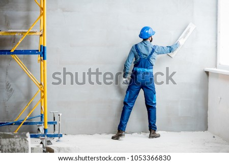 Plasterer in blue working uniform plastering the wall indoors #1053366830