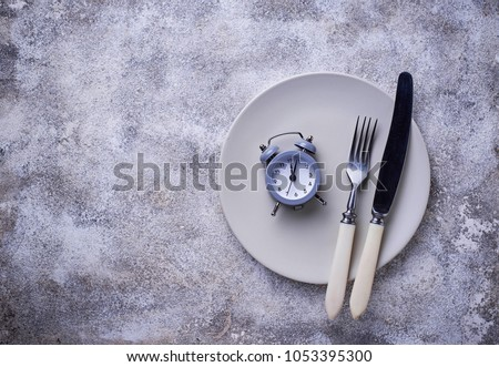 Grey alarm clock in empty plate. Lunchtime concept. Top view #1053395300