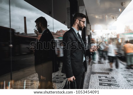 Handsome young caucasian bearded man employer in a formal suit is standing next to a bus stop and texting message on the smartphone, surrounded by city fussiness, walking people, and passing buses #1053454091