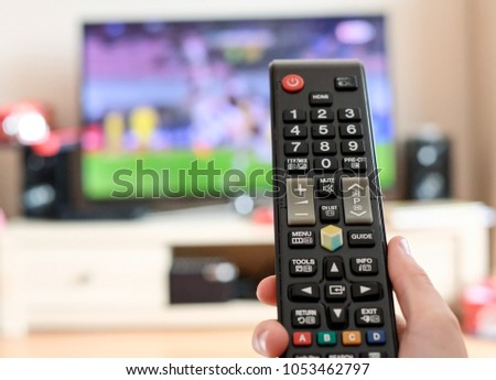 Watching TV and using remote controller #1053462797