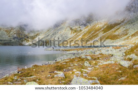 Landscape of tarn in the high mountain, grey heavy low clouds, misterious place, scenic  breathtaking beautiful view on mountaing #1053484040