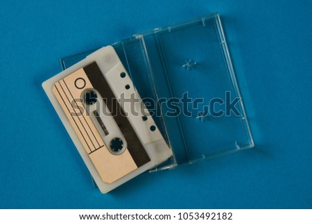 Blank cassette tape box on blue background. Vintage cassette tape case with retro cassette mockup. Plastic analog magnetic clear packaging template. Mixtape box open