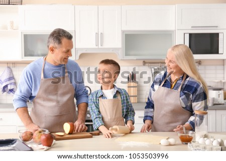 Happy senior couple with little grandson cooking together in kitchen #1053503996