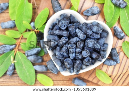 Fresh honeysuckle berries on berries and leaves background #1053601889