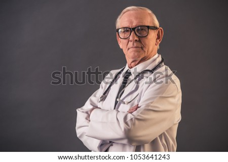 Handsome old doctor in medical coat and eyeglasses is looking at camera while standing with crossed arms on gray background #1053641243